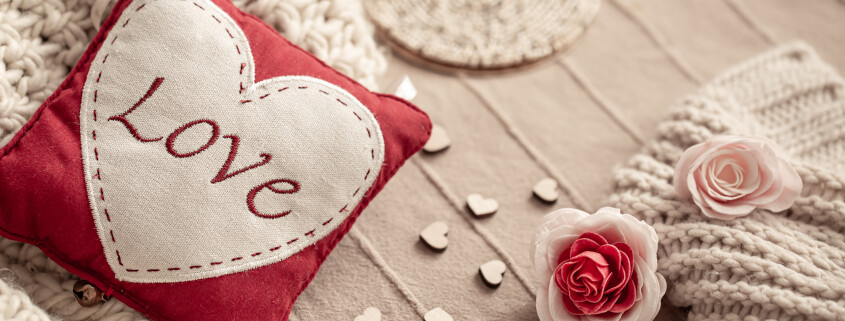 Cute composition with knitted elements and a decorative thing with the word love.