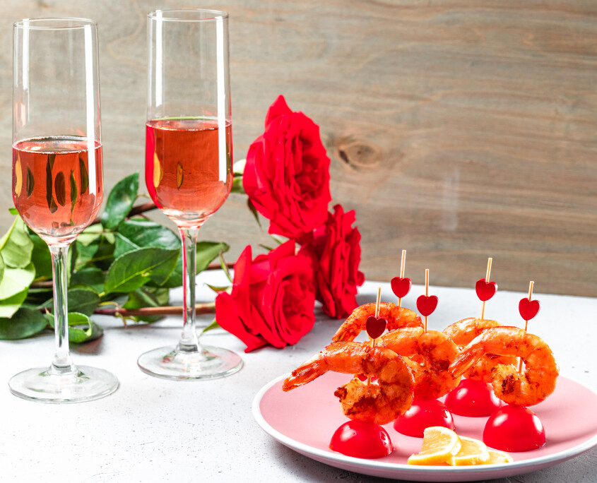 Fried shrimp, roses and champagne on the table. Original food for Valentine's Day, romantic dinner. Top view, free space for text