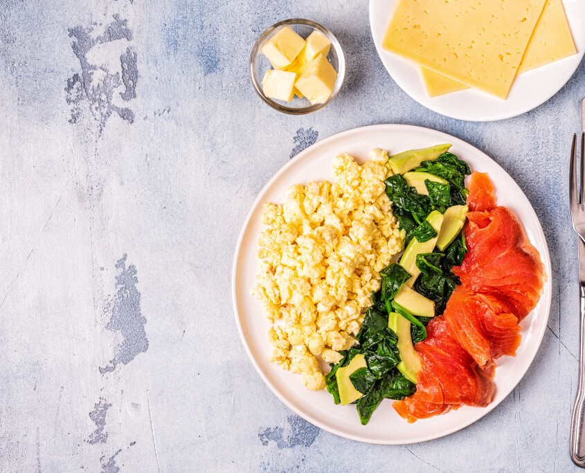 Ketogenic diet breakfast, scrambled eggs, salmon, avocado, spina