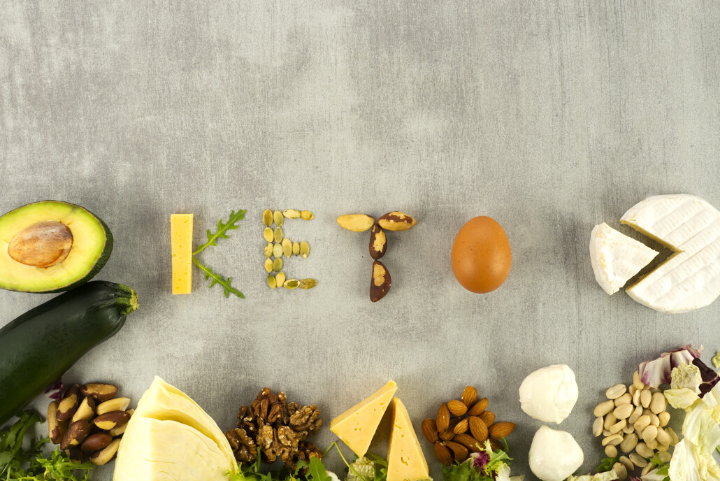 The keto word is from ketogenic food. Ketone diet foods on gray background with place for text