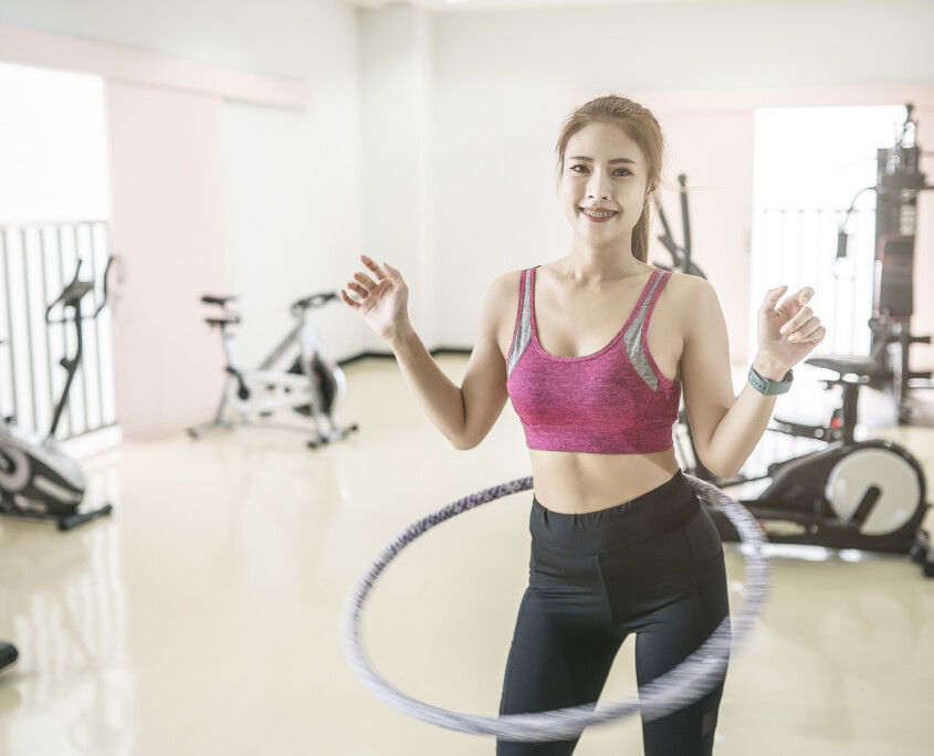 young-beautiful-asian-woman-in-sportswear-playing-hula-hoop-exercise-in-the-fitness-gym