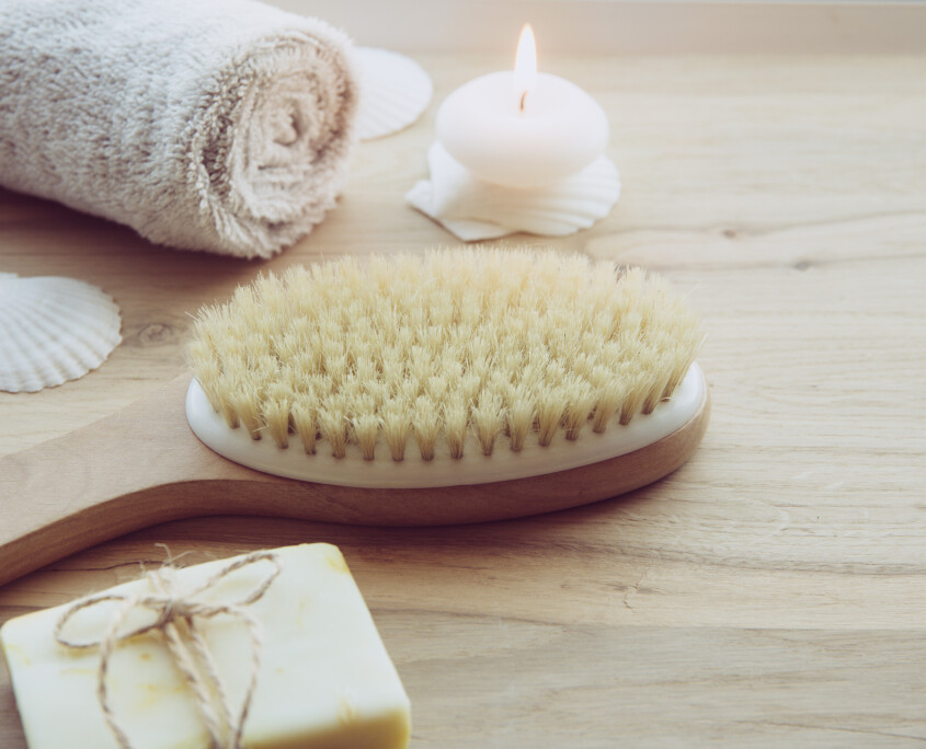 Dry brushing the skin in a pattern with a dry brush, usually before showering help reduce cellulite and remove toxins in human body. Selective focus on firm, natural bristle brush with a long handle.